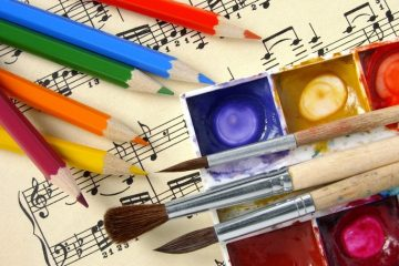A sheet of music covered in colored pencils and paints