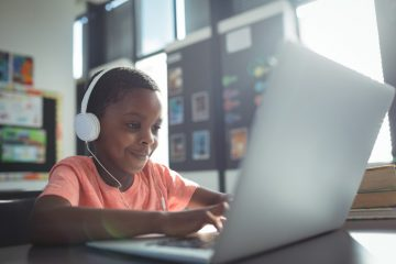 Boy listening music while using laptop