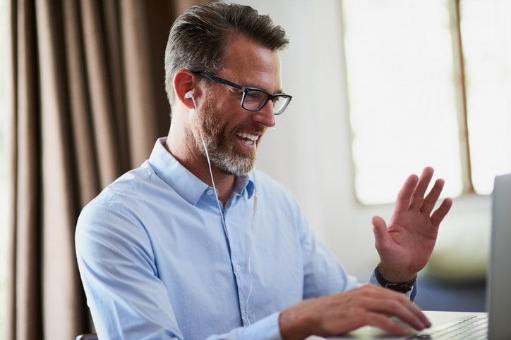 man waving at computer screen