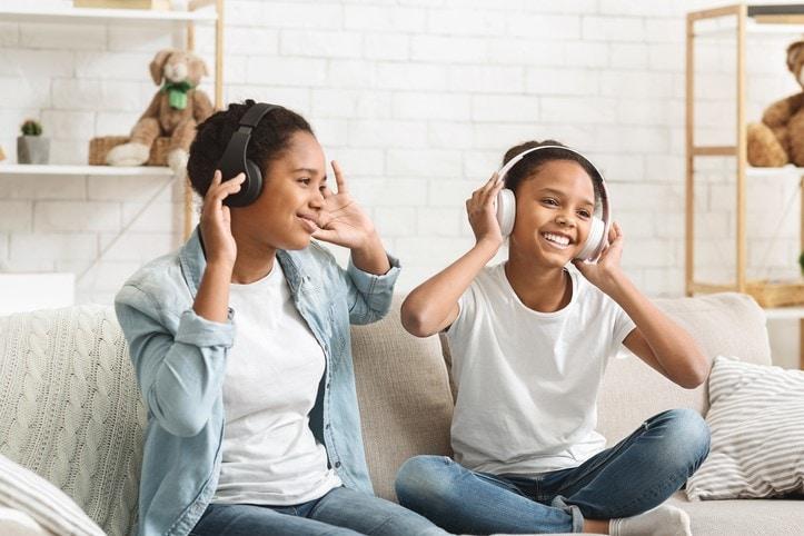 Schoolgirls listening to music with wireless headphones and dancing