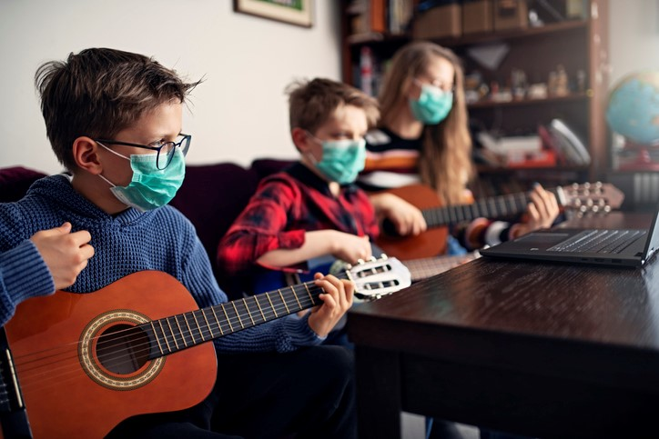 children taking at home guitar lessons online wearing masks