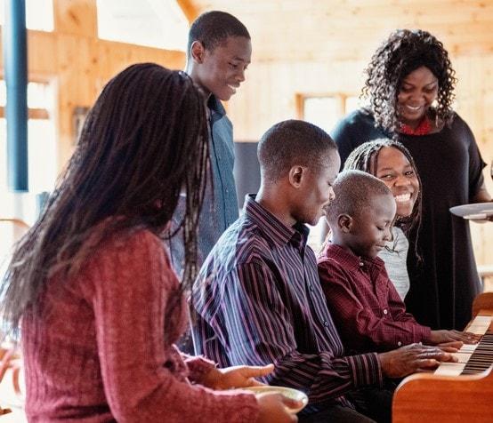 Black family singing around piano