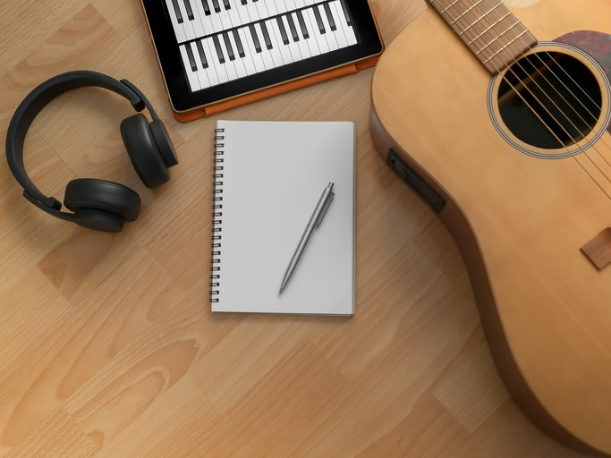 song writing with guitar headphones notebook tablet