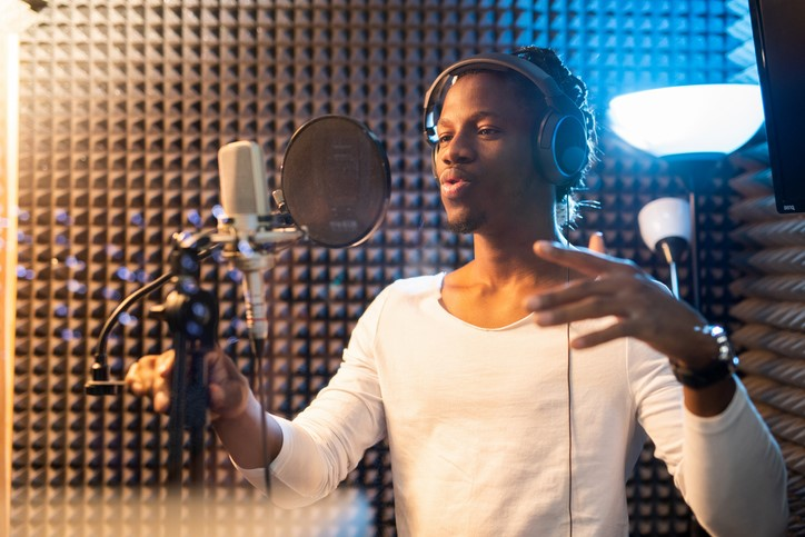 Young Black singer in studio at mic studying voice