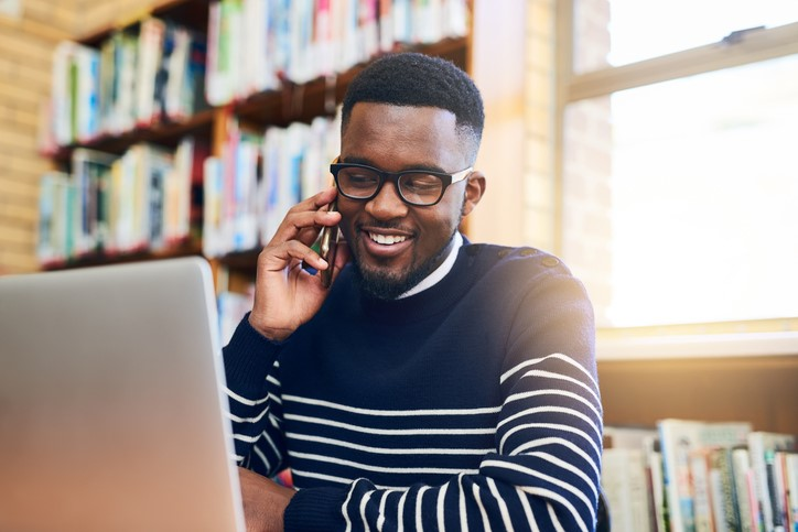 smiling Black male student on phone at laptop in library online college fairs