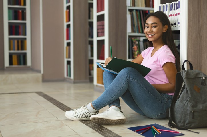Young female student in library with notebook