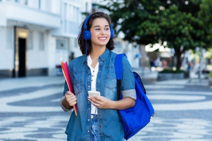 Young Latina student on campus wearing headphones holding books and backpack