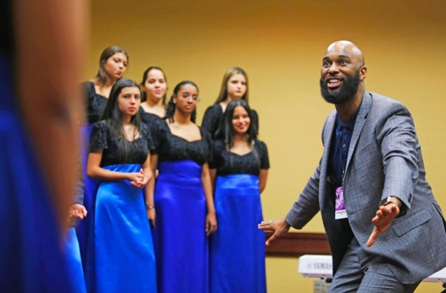 choral director with choir engaged in the artistic process