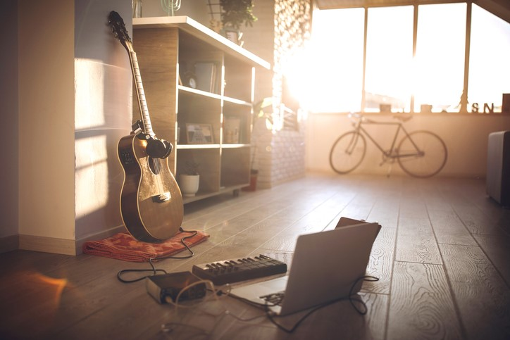 guitar and headphones with laptop in young student's room