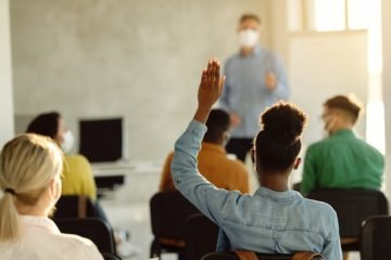 Rear view of African American student raising hand during a class
