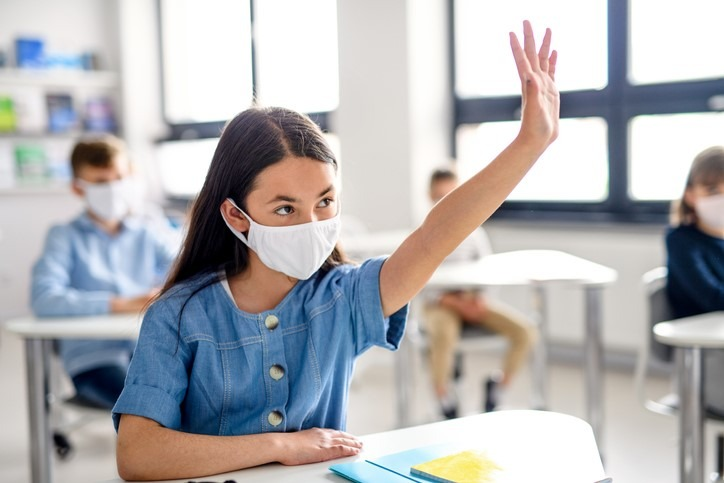 Girl with face mask raising hand
