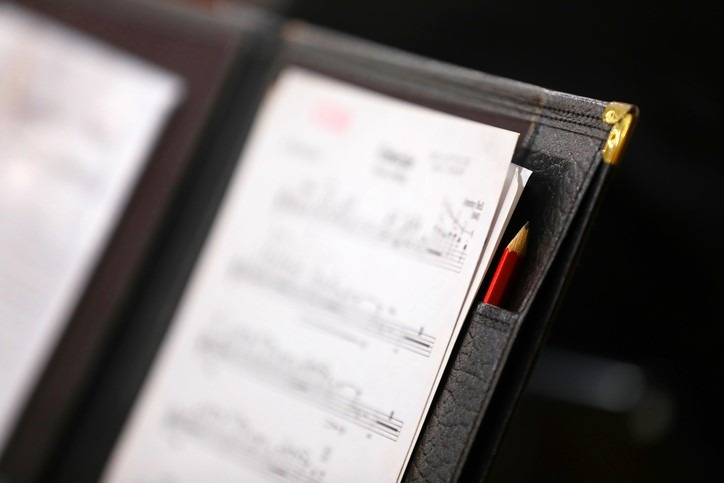 Open music score notes in a black leather folder with editing pencil