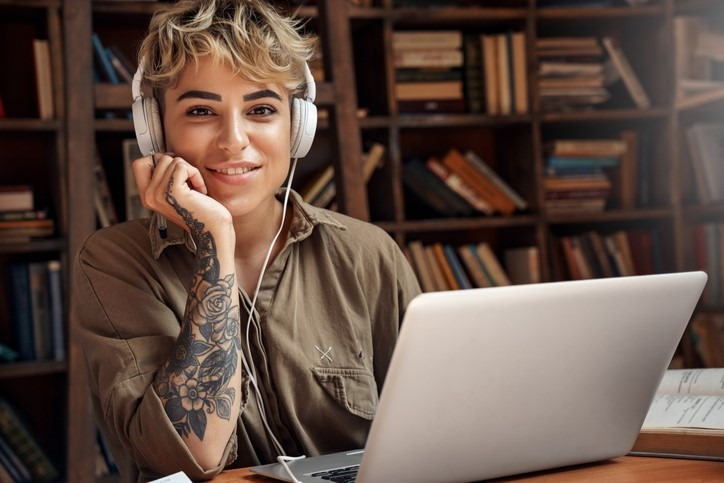 Young adult woman in headphones on laptop looking at camera