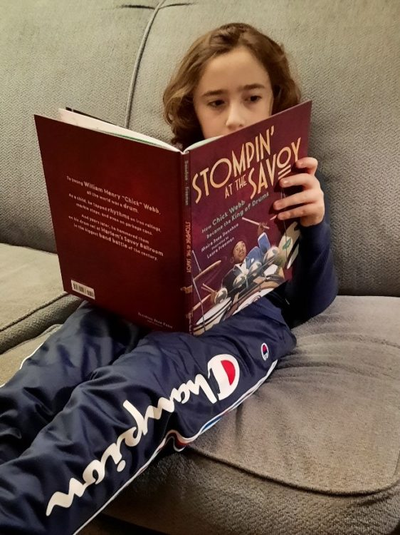 young boy reading children's picture book Stompin at the Savoy