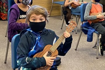 young students wearing masks playing ukuleles