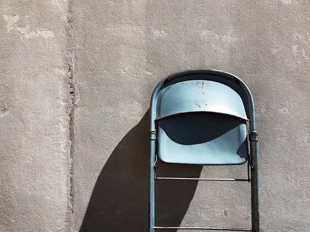 metal folding chair leaning against wall