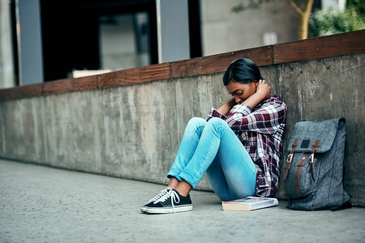 stressed female student sitting on ground