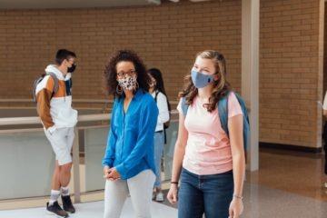 high school teacher and student in masks in school