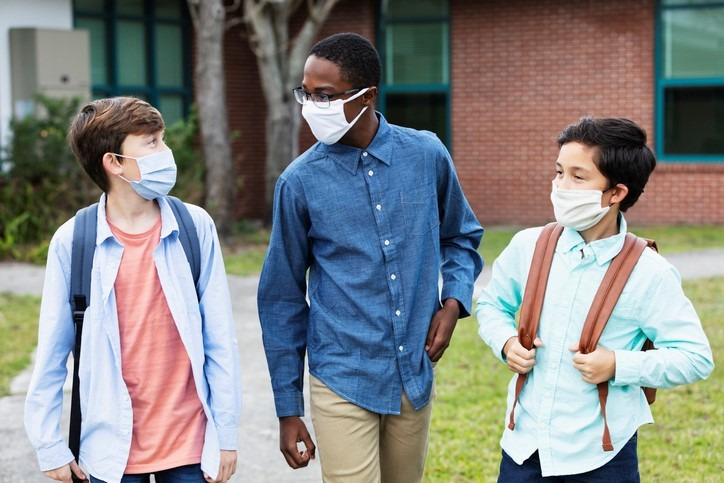 Three middle school boys walking, talking outdoors during uncertain times in learning