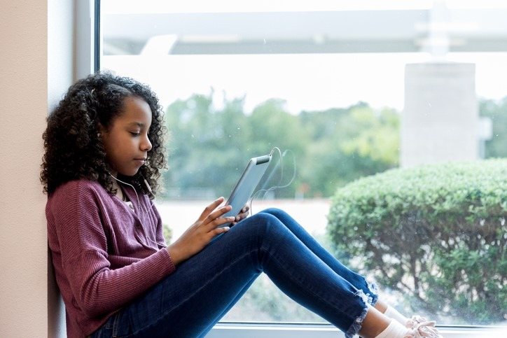Girl sits on windowsill to watch video on tablet