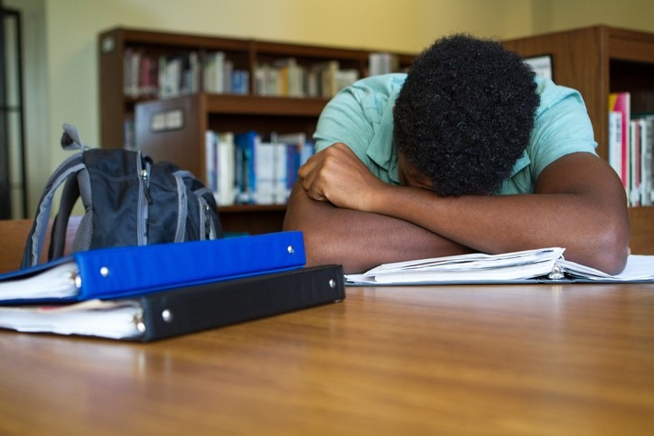 Student overwhelmed with head on desk