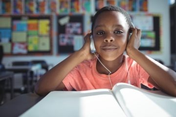 Boy listening music with headphones at desk