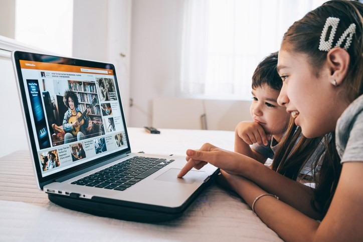 Children watching a guitar video online lesson at home in isolation using laptop
