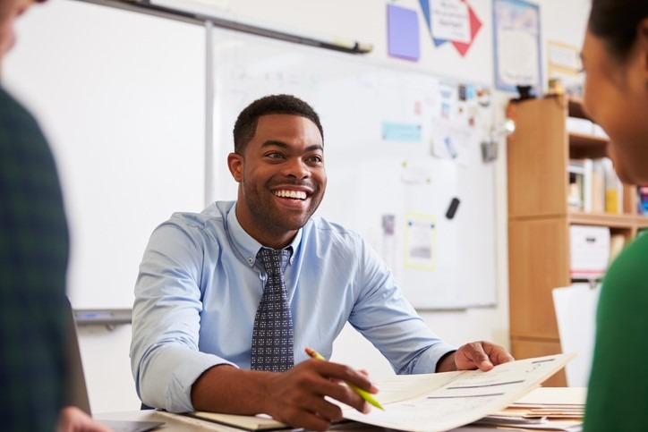 Happy teacher at desk talking to colleagues