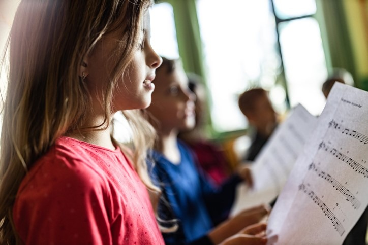 Schoolgirl practicing with sheet music in a class at school