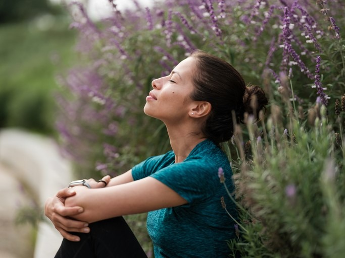 woman relaxing next to flowers