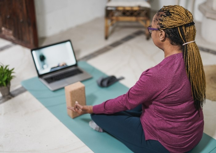 woman doing yoga at home with laptop