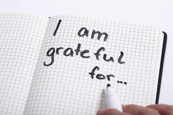 Person Writing I Am Grateful in journal