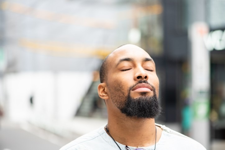 man standing outside with his eyes closed enjoying a moment of peace