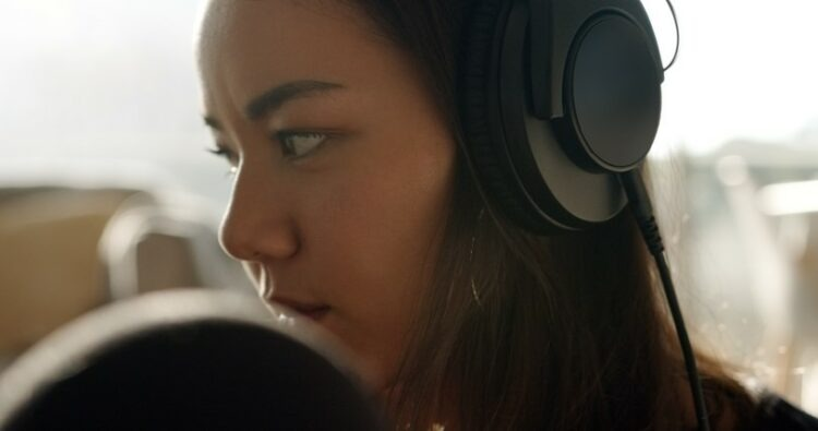 young woman practicing music at home wearing headphones