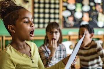 young girl singing in class