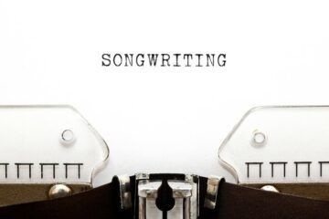 typewriter with songwriting in all caps