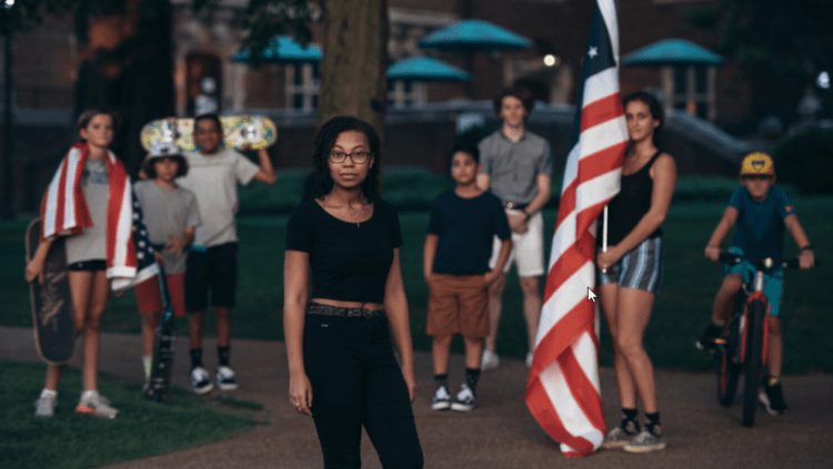 students standing facing camera holding American flags
