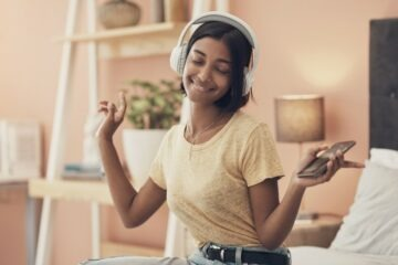 young woman with headphones listening to music on phone at home