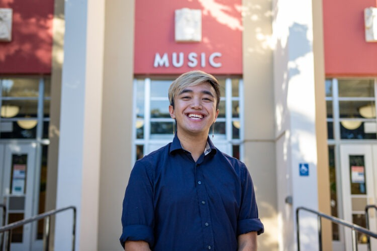 AJ Gonzales smiling outside music building
